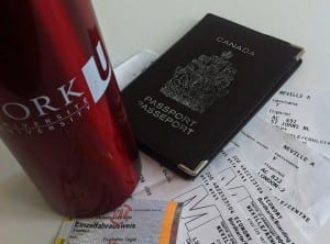 photo of Canadian passport, York University water bottle and several plane tickets