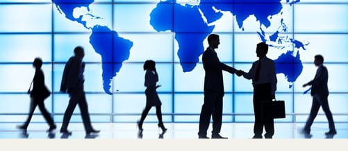 Stock image: professionals at a shaking hands and in front of a world map.